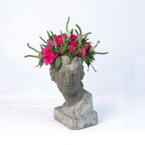 Escultura de cemento afrodita con rosas fucsia